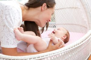 young-woman-smiling-with-newborn-infant-PU9QYYT (1)